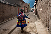 A woman spins wool as she walks in the town of Sarhua in Ayacucho, Peru.