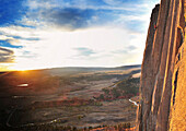 'A climber in a red shirt leading up a crack at sunrise while a women in a vest and blue shirt belays from a ledge high above the valley floor on Devil's Tower in Devil's Tower National Monument, Wyoming. A winding stream can be seen far below giving pers