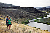 A young couple embrace as they view the Owyhee River wind through the Oregon desert.