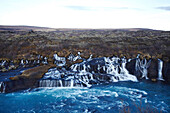Hraunfossar (Borgarfj?r ur, western Iceland) is a series of waterfalls formed by rivulets streaming over a distance of about 900 meters out of the Hallmundarhraun, a lava field which flowed from an eruption of one of the volcanoes lying under the glacier