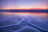 The vast expanse of salt flats in Death Valley's Badwater region photographed at sunrise.  On this year, in spring, water filled the entire playa creating the opportunity to observe the beautiful reflections of sky and Telescope peak in the shallow water