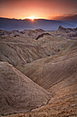 An image that depicts the essence of Death Valley's hot, harsh and unforgiving climate.  Zabriskie point, on of the park's most unique geological attractions can be seen in the upper right corner across the desolate landscape of gullies and ridges.  This
