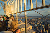Tourists at the Empire State Building viewing platform enjoying the view, Manhattan, New York City, New York, United States of America, North America