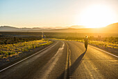 Woman walking down a long winding road at sunset in eastern Nevada, United States of America, North America