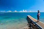 Tourist standing on a little pier with Cocos Island in the distance, Guam, US Territory, Central Pacific, Pacific