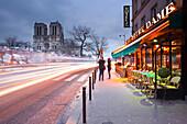 Tourists stop to photograph Notre Dame de Paris cathedral at dawn, Paris, France, Europe
