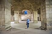 Tourist exploring the underground halls at Diocletian's Palace, UNESCO World Heritage Site, Split, Dalmatian Coast, Croatia, Europe