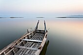 Traditional rowing boat moored on the edge of flat calm Taungthaman Lake at dawn with the colours of the sky reflecting in the calm water, close to the famous U Bein teak bridge, near Mandalay, Myanmar (Burma), Asia