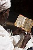 Old man wearing traditional gabi (white shawl) reading Holy Bible in rock-hewn monolithic church of Bet Medhane Alem (Saviour of the World), Lalibela, Ethiopia, Africa