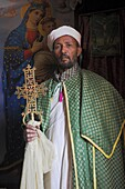Priest with cross, Bet Meskel, an excavated chapel in the northern wall of the courtyard of Bet Maryam, Lalibela, Ethiopia, Africa