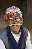 Old Nepali man wearing topi hat in Mul Cowk courtyard, posing for tourists, Durbar Square, Patan, Kathmandu Valley, Nepal, Asia