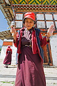 Woman spinning a prayer wheel, Jampay Lhakhang, built in 659 by Tibetan King Songtsen Gampo, Jakar, Bumthang, Chokor Valley, Bhutan, Asia