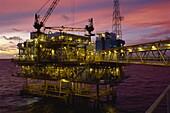 Oil rig illuminated at dusk, Gulf of Thailand, Thailand, Southeast Asia, Asia