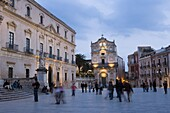 People strolling in the evening, Santa Lucia alla Badia beyond, Piazza Duomo, Ortygia, Syracuse, Sicily, Italy, Europe