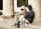 Two Cuban men in vintage forties clothes and smoking cigars while waiting for tourist photographers in Plaza de la Catedral, Habana Viejo, Havana, Cuba, West Indies, Central America