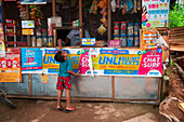 Young boy reaches for the top at grocery shop, Coron, Busuanga, Palawan, Philippines, Asia