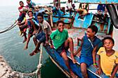 Teenagers gathering on a fishing boat, Lorengau, Manu Province, Papua New Guinea, South Pacific