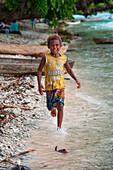 Young boy with Nike t-shirt runs along beach, Nendo Island, Santa Cruz Islands, Solomon Islands, South Pacific