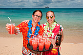 Friendly bar staff from expedition cruise ship MS Hanseatic (Hapag-Lloyd Cruises) offer tropical drinks on beach at Sandy Beach Resort, Foa Island, Ha'apai Group, Tonga, South Pacific