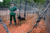 Barbed wire and figure of guard with watchdog in former prison and now museum, Phu Quoc, Mekong Delta, Vietnam, Asia