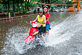 Cheerful women on scooter ride through flooded street during downpour, Ho Chi Minh City (Saigon), Ho Chi Minh, Vietnam, Asia