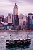 Star Ferry and skyline across Hong Kong harbor at dusk, Hong Kong, Hong Kong, Asia