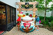 Young girl and kitschy sculpture, Hong Kong, Hong Kong, Asia