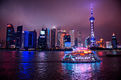 Sightseeing boat on Huangpu River with Oriental Pearl Tower and Pudong skyline at night, Shanghai, Shanghai, Asia