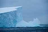 Waves crash against the ca. 30 meter tall face of a 36 kilometer long iceberg (tracking number B17A), near South Georgia Island, Antarctica