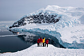 Passengers of expedition cruise ship MS Hanseatic (Hapag-Lloyd Cruises) admire view from snow-covered mountain, Neko Harbour, Graham Land, Antarctica