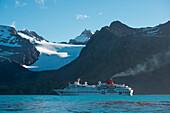 Expeditions-Kreuzfahrtschiff MS Hanseatic (Hapag-Lloyd Kreuzfahrten) vor Bergkulisse mit Gletscher, Gold Harbour, Südgeorgien, Antarktis