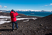 Man in red expedition parka stands at crater edge and takes a photograph of expedition cruise ship MS Hanseatic (Hapag-Lloyd Cruises), Telephone Bay, Deception Island, South Shetland Islands, Antarctica