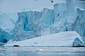Passengers in a Zodiac dinghy of expedition cruise ship MS Hanseatic (Hapag-Lloyd Cruises) are dwarfed by an iceberg and the edge of the glacier, Paradise Bay (Paradise Harbor), Danco Coast, Graham Land, Antarctica