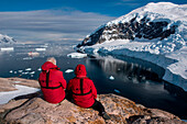 Passengers from expedition cruise ship MS Hanseatic (Hapag-Lloyd Cruises) sit on rock and admire view from hilltop, Neko Harbour, Graham Land, Antarctica
