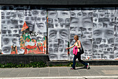 Woman walks in front of mural featuring dozens of eyes, Ushuaia, Tierra del Fuego, Patagonia, Argentina