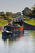 A canal boat leaving the famous series of locks at Caen Hill on the Kennet and Avon Canal, Wiltshire, England, United Kingdom, Europe