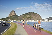 People exercising on pathway around Botafogo Bay with Sugar Loaf Mountain (Pao de Acucar) in the background, Rio de Janeiro, Brazil, South America