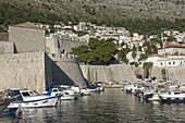 Boats moored in the shelter of the walls of the Old City, Dubrovnik, UNESCO World Heritage Site, Croatia, Europe