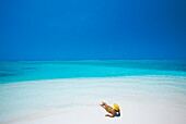 Woman reading a book on the beach, Maldives, Indian Ocean, Asia