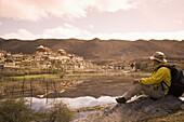 Chinese man trekking and looking at Ganden Sumsteling Gompa (Gandan Sumtseling) (Songzanlin Si) Buddhist Monastery, Shangri-La, formerly Zhongdian, Yunnan Province, China, Asia