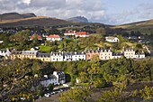 Houses on hillside overlooking the harbour, the Storr visible on horizon, Portree, Isle of Skye, Highland, Scotland, United Kingdom, Europe