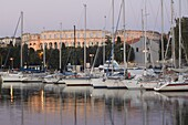 Yachts in the harbour, with the 1st century Roman amphitheatre beyond in evening light, Pula, Istria coast, Croatia, Adriatic, Europe