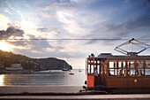 Tram at sunset set against yachts in bay, Soller, Mallorca, Balearic Islands, Spain, Mediterranean, Europe