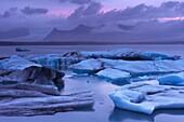 Icebergs in Jokulsarlon glacial lagoon, at dusk, Oraefajokull (Vatnajokull) glacier in the distance, East Iceland, Iceland, Polar Regions