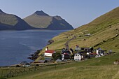 Village of Kunoy, located on the west coast of the island Kunoy, impressively surrounded by high mountains, Kunoy Island, Nordoyar, Faroe Islands (Faroes), Denmark, Europe