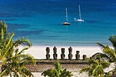 Anakena beach,  yachts moored in front of the monolithic giant stone Moai statues of Ahu Nau Nau,  four of which have topknots,  Rapa Nui (Easter Island),  UNESCO World Heritage Site,  Chile,  South America