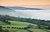 Isolated farm on a valley slope on a misty dawn,  Brecon Beacons National Park,  Powys,  Wales,  United Kingdom,  Europe