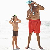 Grandfather and grandson (6-8) on beach with snorkelling masks