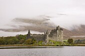 View across Loch Awe to the ruins of Kilchurn Castle, early morning mist on mountains, Dalmally, Argyll and Bute, Scotland, United Kingdom, Europe
