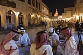 A group of men in Arabian dress in the restored Souq Waqif, Doha, Qatar, Middle East